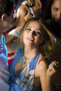 Gorgeous woman in smart dress dancing in crowd of clubbers
